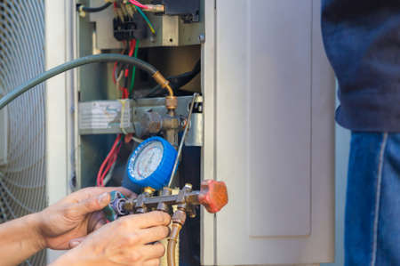 Air Conditioning Repair man hands checking and fixing modern air conditioning system, Technician team checking leakage air conditioning system