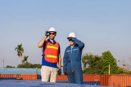 Factory worker man in hard hat and safety vest and foreman checking control loading containers box from cargo, Teamwork concept Фото со стока