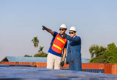 Factory worker man in hard hat and safety vest and foreman checking control loading containers box from cargo, Teamwork concept