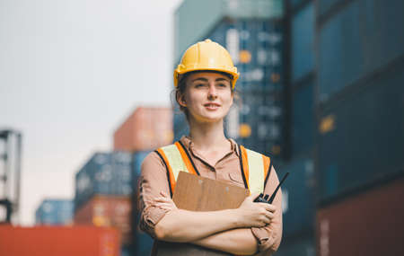 Woman Foreman in hardhat and safety vest holding clipboard checklist and two-way radio aat containers cargo Stock Photo