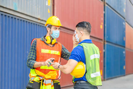 Factory worker man checking fever by digital thermometer for scan and protect from Coronavirus (COVID-19) at cargo containers - Healthcare Concept Banco de Imagens