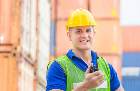Happiness foreman in hardhat and safety vest talks on two-way radio control loading containers box from cargo Stock Photo