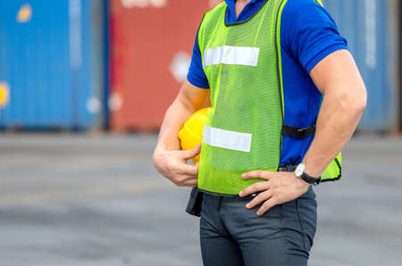 Close up of Engineer, worker man holding hard hat at cargo containers