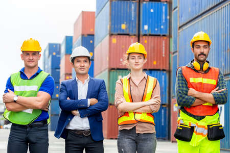 Success Teamwork Concept, Business people engineer and worker team standing with arms crossed as sign of success blurred container box background Standard-Bild