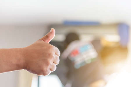 Close up of Air Conditioning repair man hand giving thumb up as sign of success, repairman fixing air conditioning system
