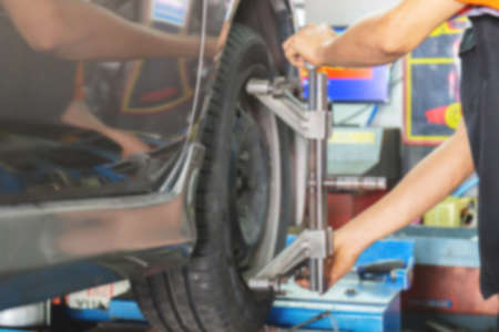 Blurred of Mechanic fixing the wheel alignment device onto a car wheel