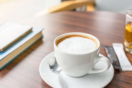 Selective focus of a coffee latte in white cup on wooden table with blurred book and smartphone in coffee shop