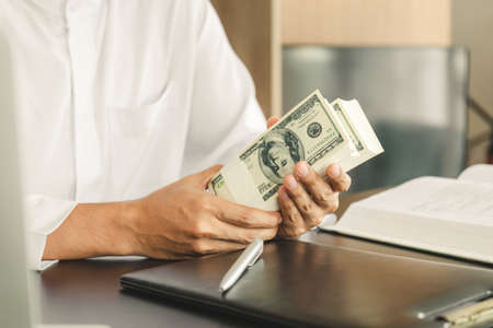 Young business muslim man holding and showing money banknotes, finance concept.