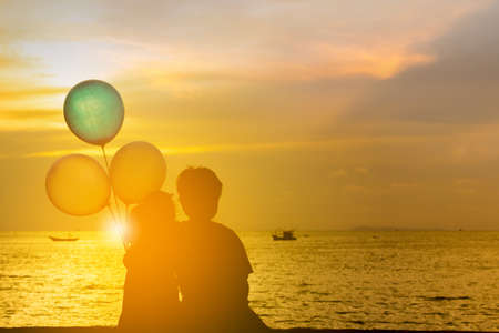 Silhouette of brother and sister sitting on the beach watching sunset with balloon in hand. Banque d'images