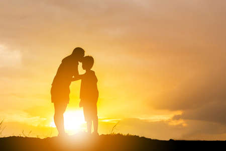 Silhouette of a mother kissing his son in a forehead on the sunset summer day. Banque d'images