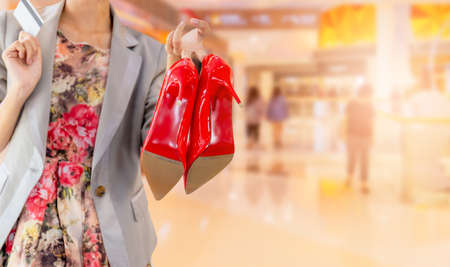 Close-up of young woman carrying shoe and credit card with shopping mall blerred background. Happy Life Style Concept.