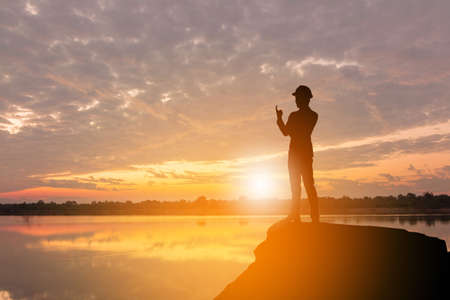 Silhouette of Business Engineer Man Celebration Success Happiness on a Stone Evening Sky Sunset at Lake Background, I am number one and active life Concept. Imagens