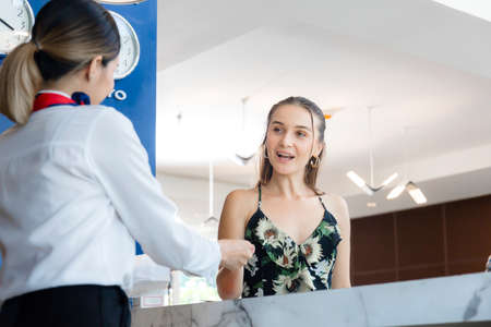 Happy guest and receptionist at hotel reception, Young travellers standing at reception desk with female receptionist standing at hotel counter