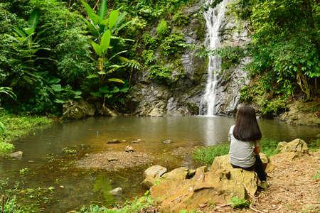 A traveler relax near ThanThip Waterfall, waterfall in deep forest near Mekong river. Nong Khai province Thailand.