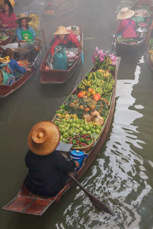 DAMNOEN SADUAK, THAILAND - 25 Jan, 2017: Damnoen saduak floating market is famous in Thailand and sights and sale of vegetables, fruits and desserts.
