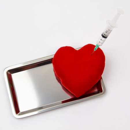 aluminum: Syringe injecting a red heart on aluminum tray.