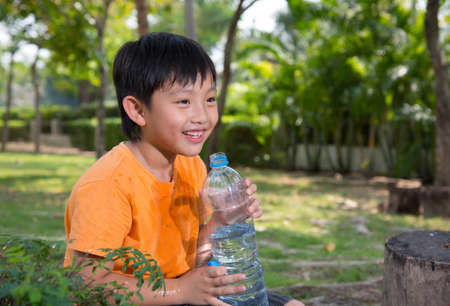 sediento: asiático bebida del agua Chico naturaleza parque cansado sed felices al aire libre