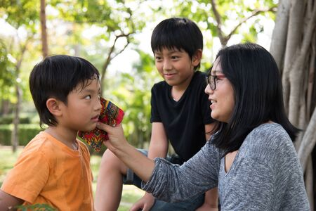 take care: asian family take care park son mother outher boy