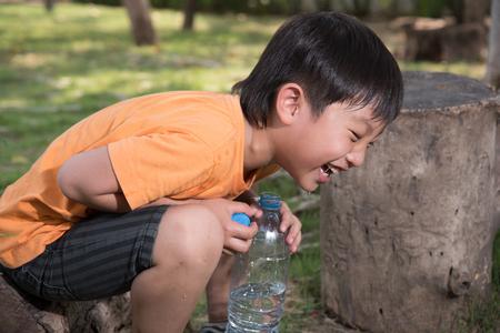 sediento: asi�tico bebida del muchacho parque acu�tico al aire libre sed naturaleza cansada risa se asfixian