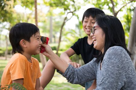 take care: asian family take care happy cute park mother son Stock Photo