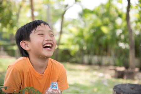 sediento: asiático agua de la bebida del muchacho sediento naturaleza cansada parque risa feliz linda