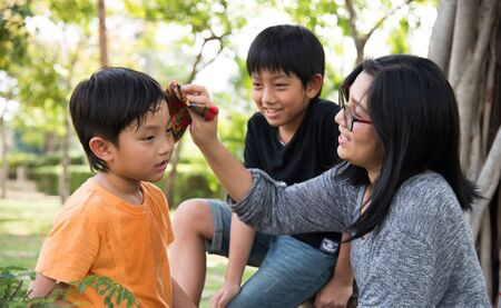 take care: asian family take care happy sweat park mother son boy outdoor
