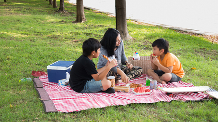 asian family picnic sitting park happy outdoor food eating kids mother son vacation fun Stock Photo