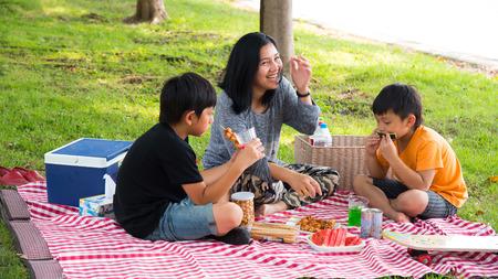 asiatische Familie Picknick essen glücklich Spaß prak im Freien Gras Urlaub Mutter Sohn Standard-Bild