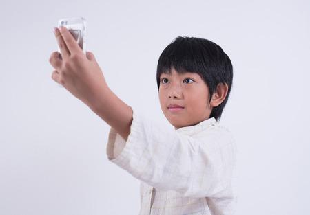 phon: asian boy phon mobile child smartphone selfie pyjamas technology Stock Photo