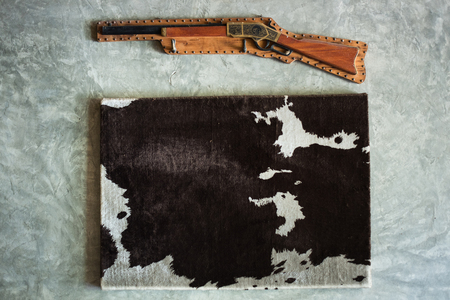 antique rifle: cow skin black white frame wool antique rifle decorte wall mortar Stock Photo
