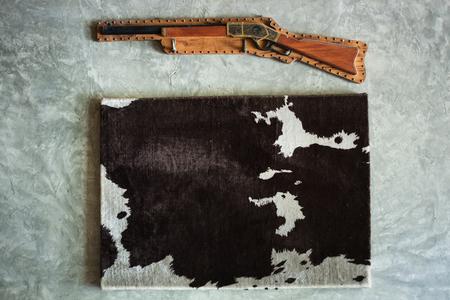 cow skin: cow skin black white frame wool antique rifle decorte wall mortar Stock Photo