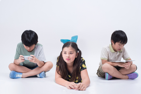 preoccupied: asian kids playing tablet phone online young social children girl boy preoccupied