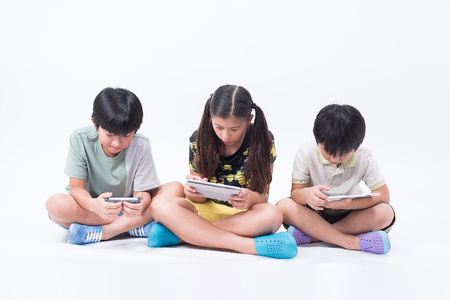 preoccupied: kids play playing tablet phone together online young social children boy girl asian Stock Photo