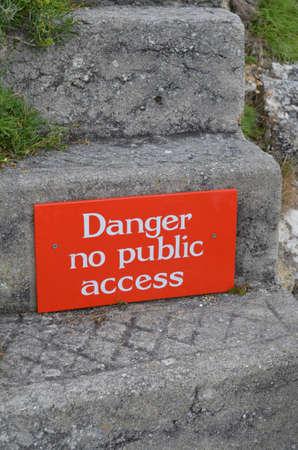 Danger no public access sign on stone step. Banco de Imagens