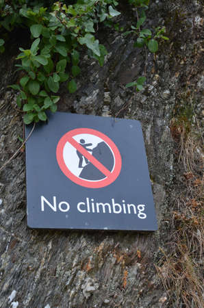 No climbing sign attached to rock face.