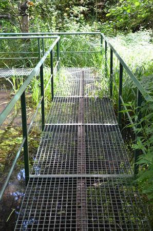 Metal walkway across water.