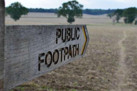 Wood public footpath direction signpost.