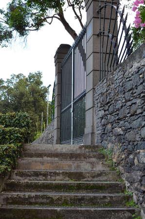 Stone steps leading to ornate iron gates.