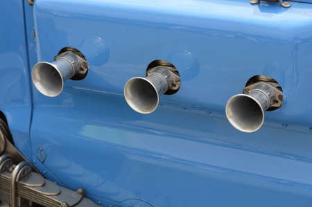 Side air filter intake pipes on a classic race car.