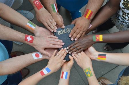hermanos internacionales y hermanas en Cristo con diferentes banderas pintadas en sus brazos que sostienen una biblia juntos Foto de archivo
