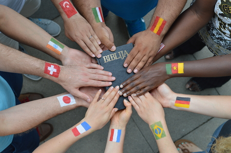 praying at church: International brothers and sisters in Christ with different flags painted on Their arms holding a bible together