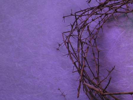 crown icon: helped crown of thorns on purple background with negative space on the left side Stock Photo