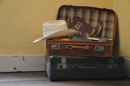 Suitcase filled with clothes, hat and a bible