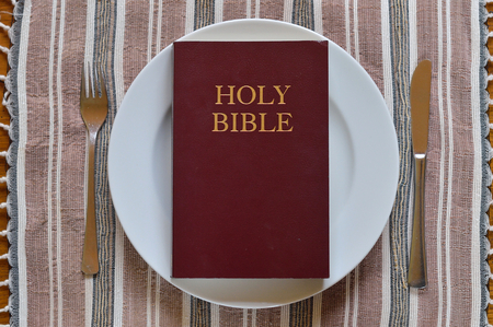 Bible on a dinner plate with silverware in lent