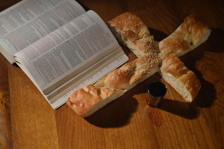 to partake: Bread in the shape of a cross with a bible open at Luke 22