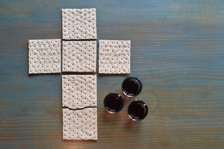 The Lord's Supper with bread in the shape of a cross and three little cups of wine