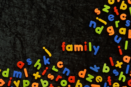 schoolkid: the word FAMILY written with colorful magnetic letters on black ground