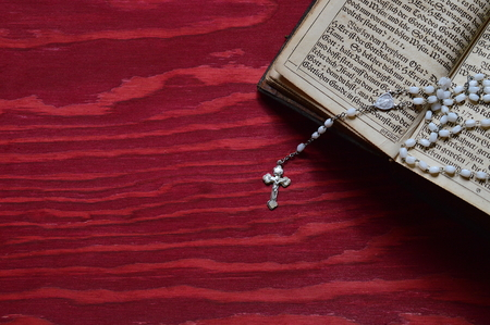 time bound: rosary with very old ancient book in old German lettering on red wooden table Stock Photo