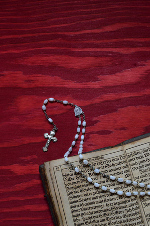 oft: rosary with very old ancient book in old German lettering on red wooden table Stock Photo