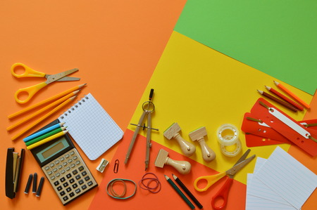School supplies on colorful paper board as border